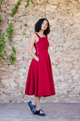 Picture of woman wearing red linen pinafore dress with straps and pockets