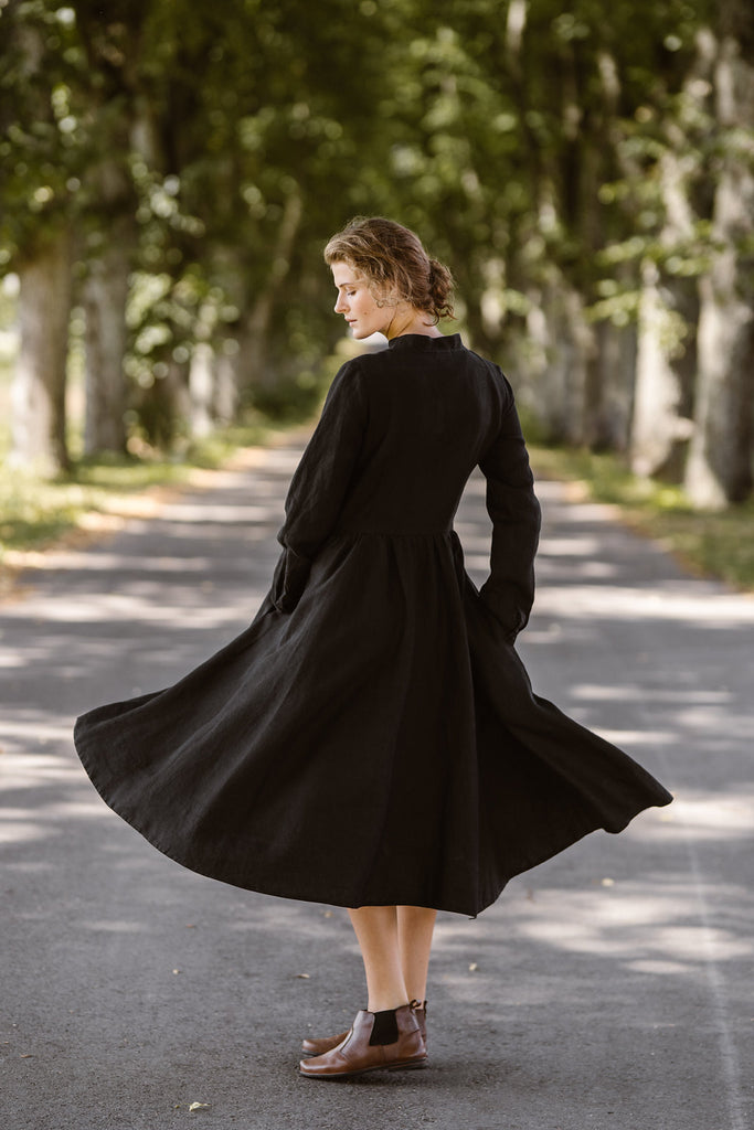Woman wearing black dress with long sleeves, picture from the side.
