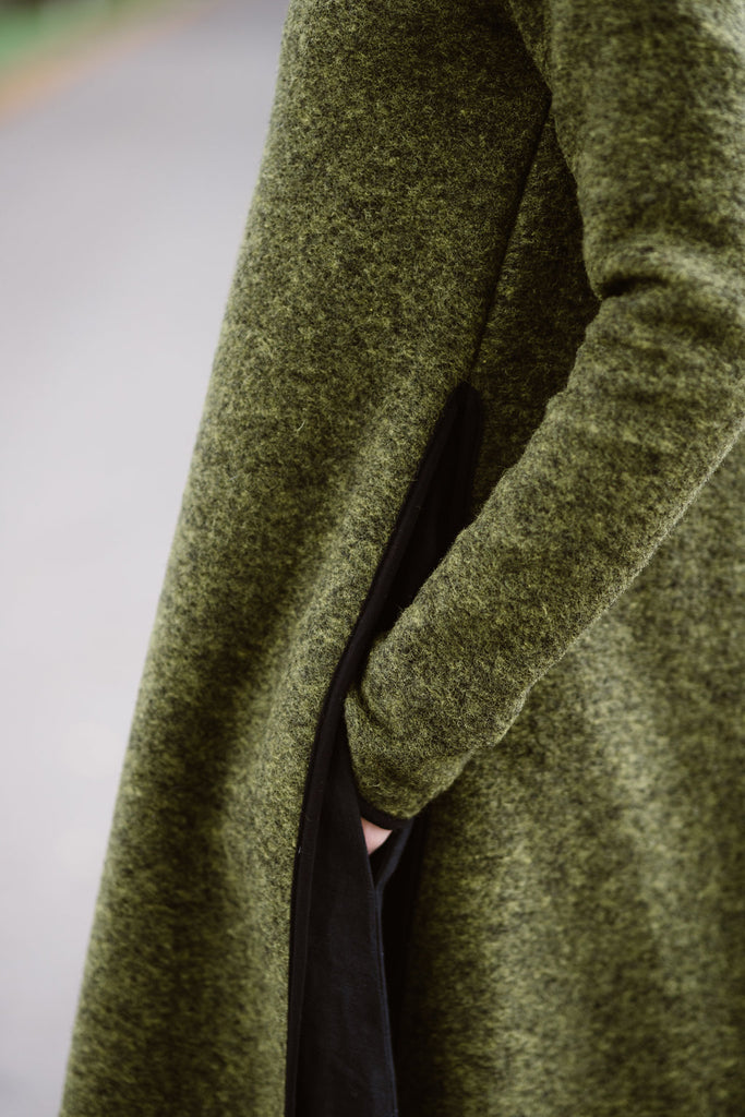 Woman wearing green color long wool sweater, up close image of a pocket