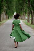 Woman wearing green color classic dress with short sleeves, picture from the back