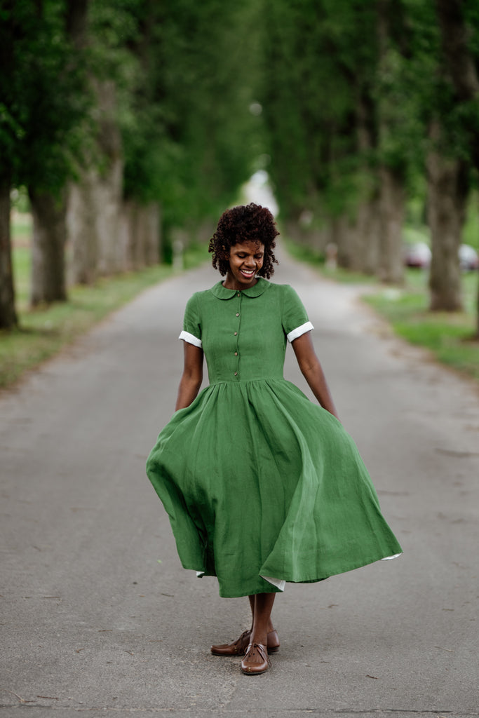 Woman wearing green color classic dress with short sleeves, picture from the front