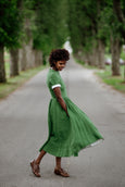 Woman wearing green color classic dress with short sleeves, picture from the side