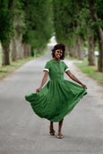 Woman wearing green color classic dress with short sleeves, image from the front