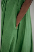 Woman wearing green color classic dress with short sleeves, up close image of a pocket
