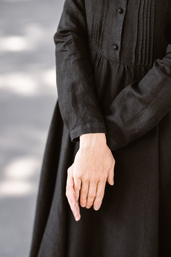 Woman wearing black dress with long sleeves, up close image from the front.