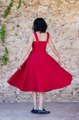 picture from the back: woman wearing red linen pinafore dress