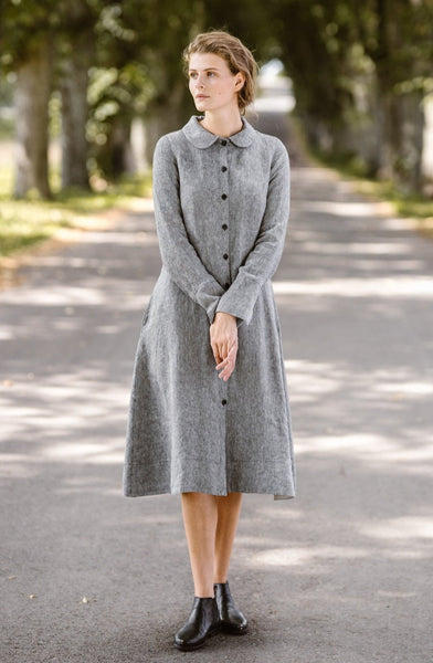 Woman wearing grey twill linen button down dress with long sleeves, picture from the front.
