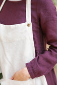 Woman wearing traditional white linen apron, up close image from the front