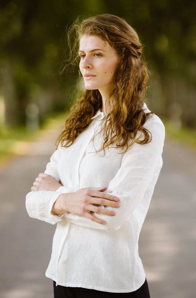 Woman wearing white minimalist linen shirt with long sleeves, image from the side