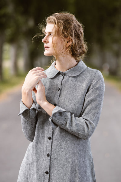 Woman wearing a grey twill linen button down dress with long sleeves, picture from the front.