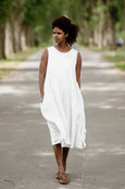 Woman wearing white sleeveless smock dress, picture from the front