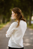 Woman wearing white minimalist linen shirt with long sleeves, image from the back