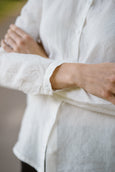 Woman wearing white minimalist linen shirt with long sleeves, up close image from the front