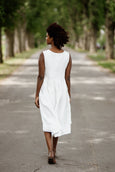 Woman wearing white sleeveless smock dress, picture from the back