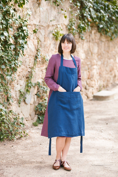 Woman wearing blue color traditional linen apron, image from the front