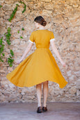 Photo from the back: woman wearing yellow linen dress with rolled up white sleeves