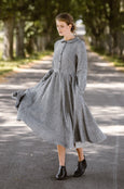Woman wearing twill linen classic dress with long sleeves, image from the front.