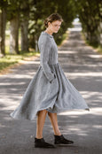 Woman wearing twill linen classic dress with long sleeves, picture from the side.