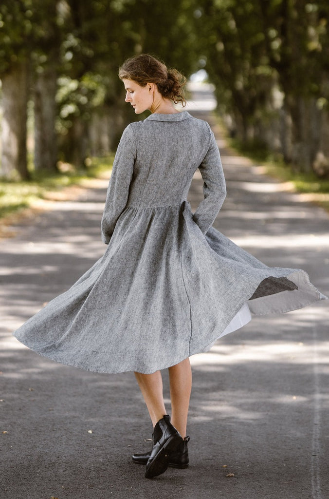 Woman wearing twill linen classic dress with long sleeves, picture from the back.