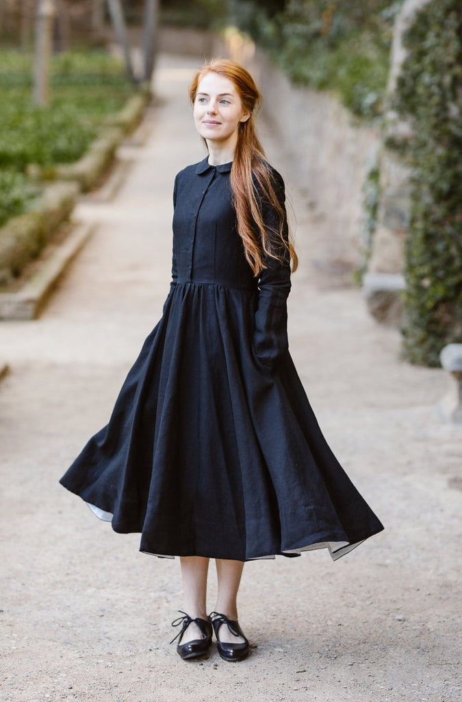 Model wearing classic black dress with long sleeves, image from the front.