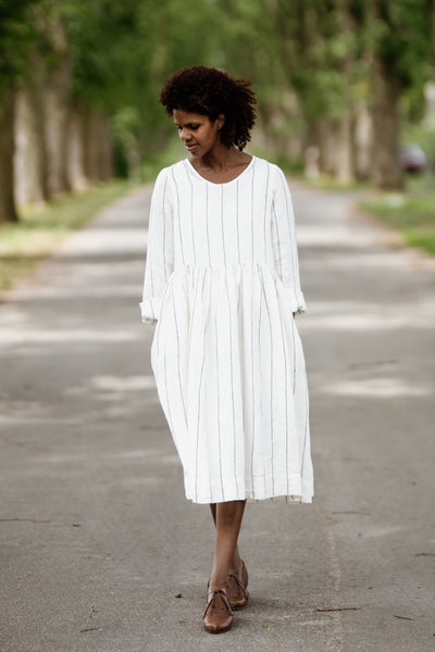 Woman wearing white smock dress with long sleeves, picture from the front.