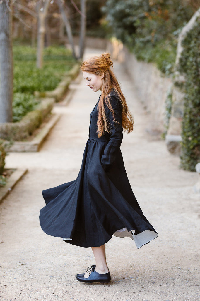 Model wearing classic black dress with long sleeves, image from the side.