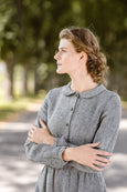 Woman wearing twill linen classic dress with long sleeves, up-close image from the front.