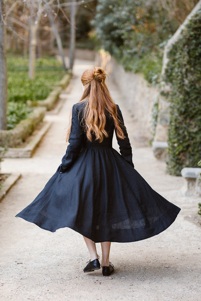 Model wearing classic black dress with long sleeves, image from the back.