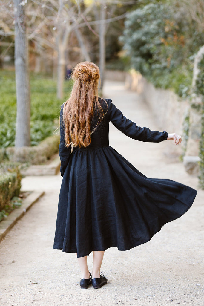 Woman wearing classic black dress with long sleeves, image from the back.