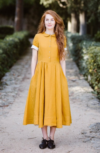 Woman wearing yellow classic dress with short sleeves, picture from the front.