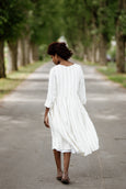 Woman wearing white smock dress with long sleeves, image from the back.