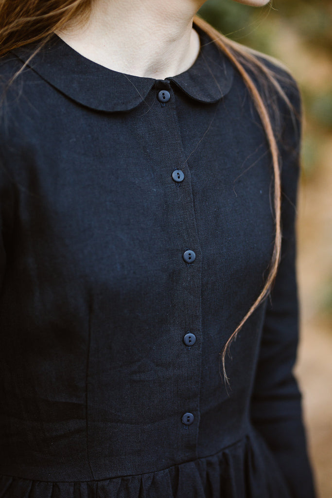 Woman wearing classic black dress with long sleeves, up-close image from the front.