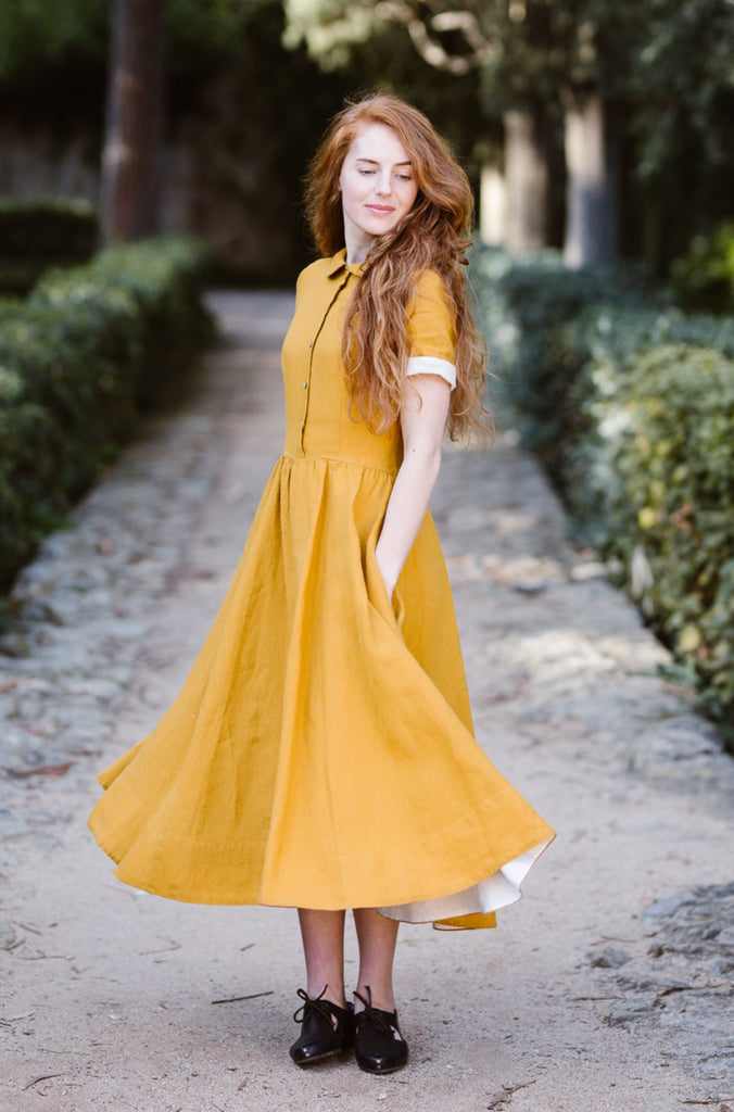 Woman wearing yellow classic dress with short sleeves, image from the front.