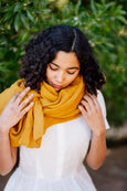Picture of woman wearing turmeric yellow linen shawl