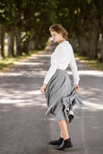 Woman wearing grey color twill midi skirt, image from the side