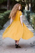 Woman wearing yellow classic dress with short sleeves, picture from the back.
