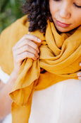 Up close detail of linen scarf in marigold yellow