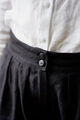 Woman wearing blue color minimalist linen shirt with long sleeves, image from the back
