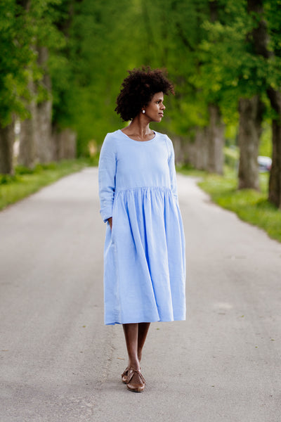 Woman in light blue linen dress with high waist and long sleeves