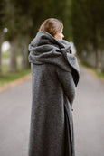 Woman wearing grey color wool shawl, image from the side