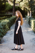 Woman wearing black classic dress with short sleeves, picture from the side