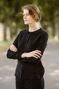 Woman wearing black minimalist linen shirt with long sleeves, image from the side