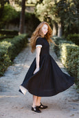 Model wearing black classic dress with short sleeves, picture from the side