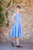 Side picture of light blue linen dress with straps, buttoned side and pockets
