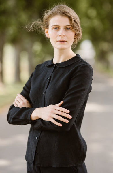 Woman wearing black minimalist linen shirt with long sleeves, image from the front