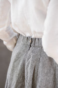 Woman wearing grey color twill midi skirt, up close image from the back