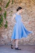Photo from the side of woman turning in light blue linen dress
