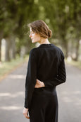 Woman wearing black minimalist linen shirt with long sleeves, image from the back