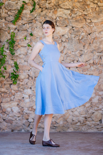 Woman wearing light blue linen dress with straps