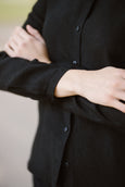 Woman wearing black minimalist linen shirt with long sleeves, up close image from the front